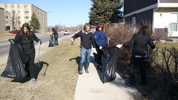 Frontiers North team members helping clean up a park for Earth Day.