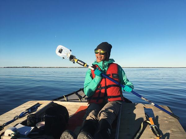 Justine on a boat on the Churchill River holding a device used in her studies.