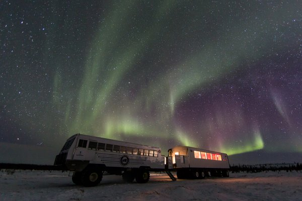 A Tundra Buggy® sits on the icy tundra with an active aurora overhead.