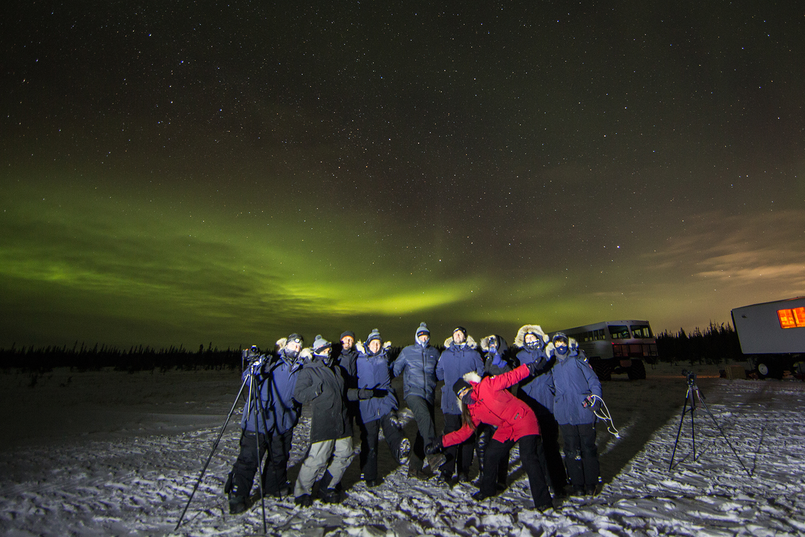 A group of new friends beneath the northern lights in Churchill, Manitoba, Canada.