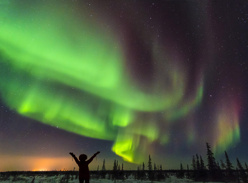 A person stands below an active northern lights display