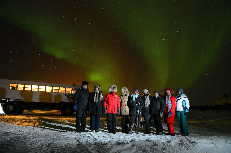 A group of guests stand under the northern lights near a Tundra Buggy.