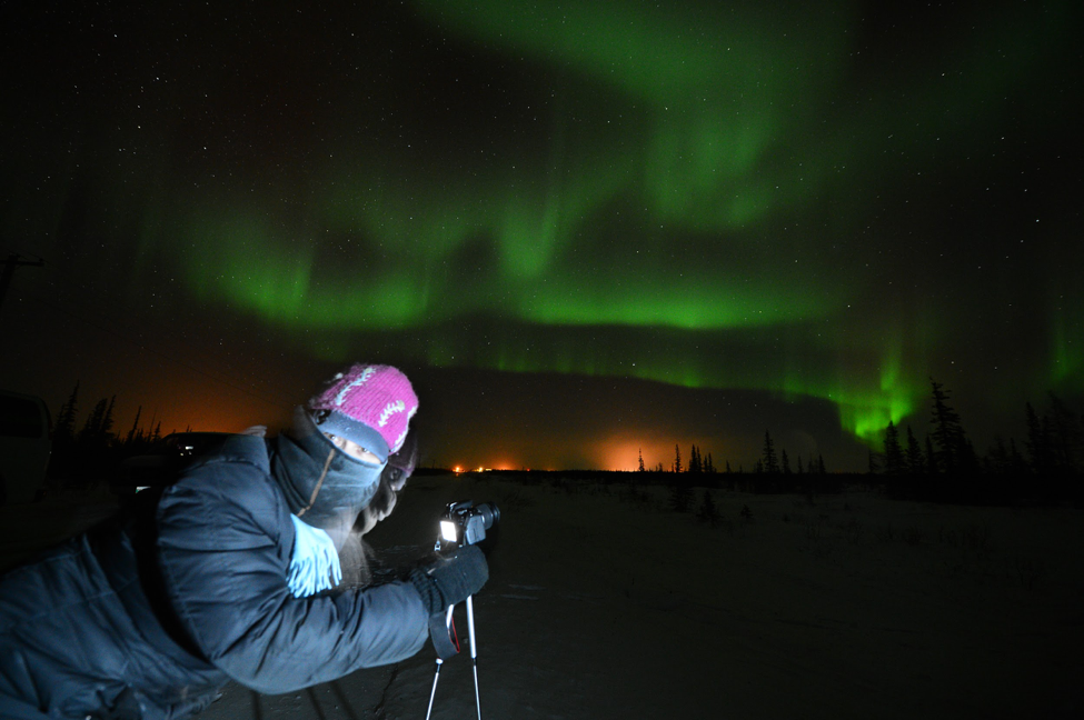 A guest prepares their camera to capture a photo of the aurora.