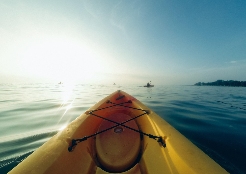 An image taken from the bow of a kayak on calm water in bright sunlight.