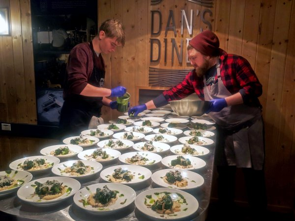Chef Jared Fosser and sous chef finish plating dishes for guests.