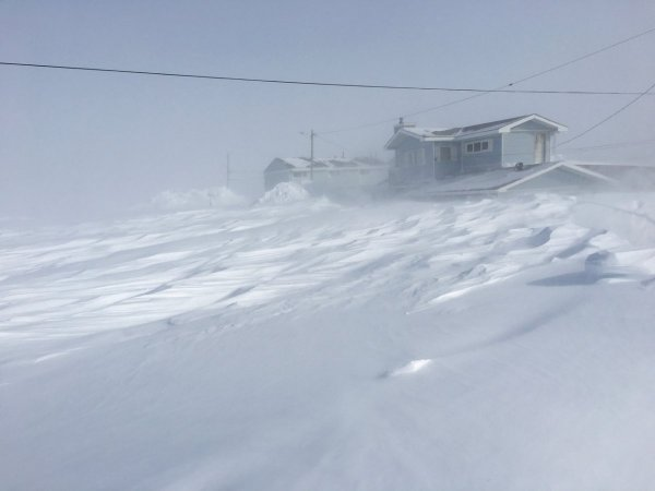A large drift of blown snow nearly as high as the first floor on a nearby house during a blizzard