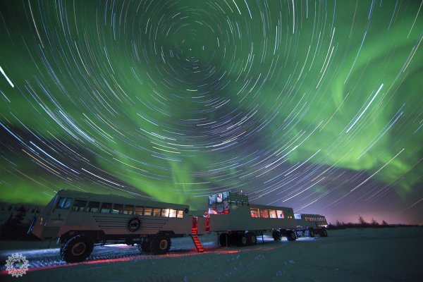 A timelapse photograph of the northern lights with a Tundra Buggy® and the lounge car from our Lodge.