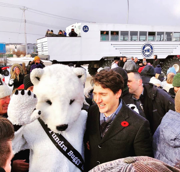 Justin Trudeau stands smiling amongst a crowd with his arm around a person in a bear costume. A Tundra Buggy® sits on the road in the background.